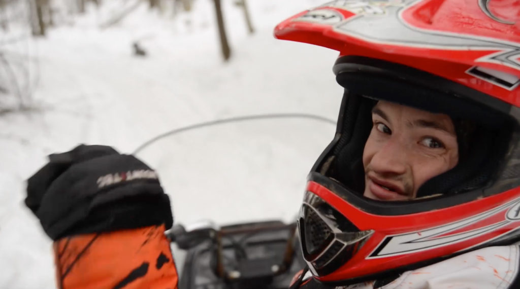 Travis looking at the camera while on snowmobile.