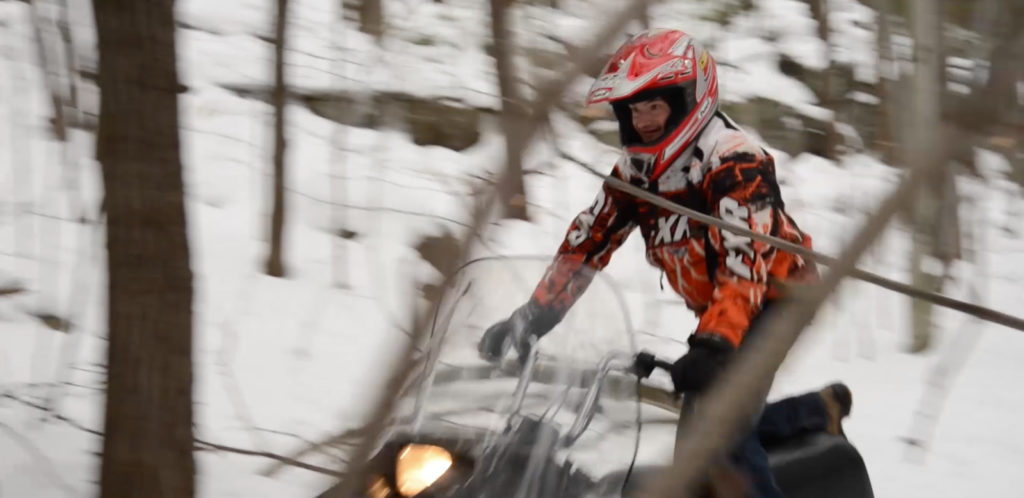 Travis riding through a forest on a snowmobile.