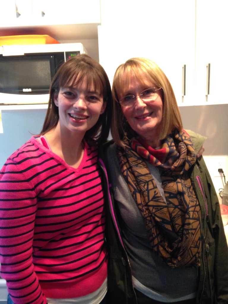Stacey and her mother standing in Stacey's kitchen, both smiling.