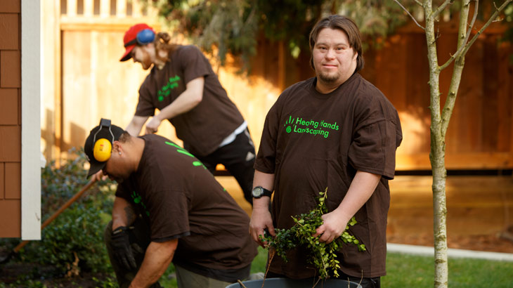 Employee with an intellectual disability landscapes with coworkers