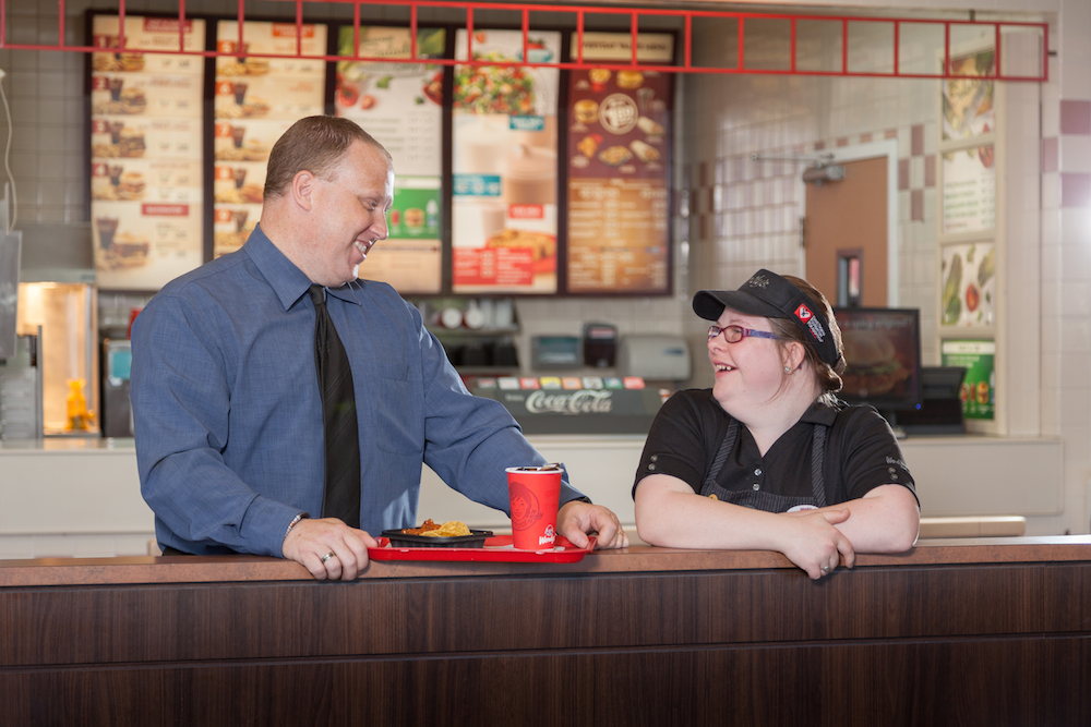 Wendy's female employee with Down syndrome smiling with her supervisor.