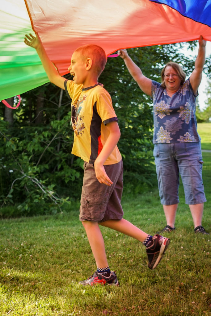 Boy with intellectual disability playing outside with others.