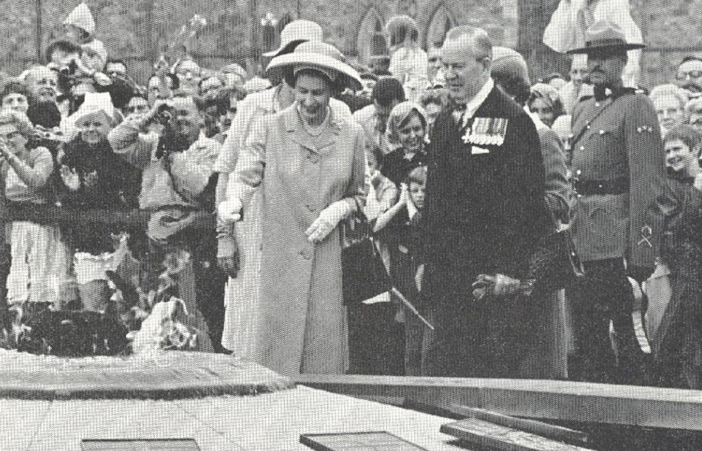 Queen throwing coin into Centennial Flame in Ottawa