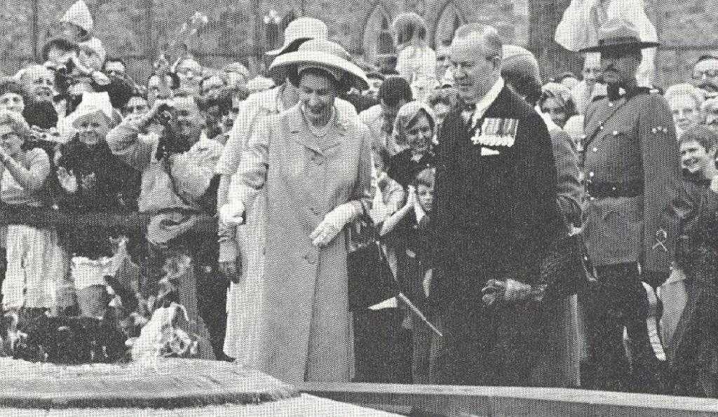 Queen throwing coin into Centennial Flame in Ottawa