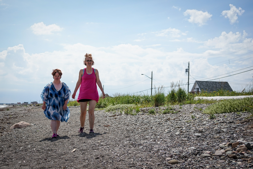 Two female friends walking along a beach together.