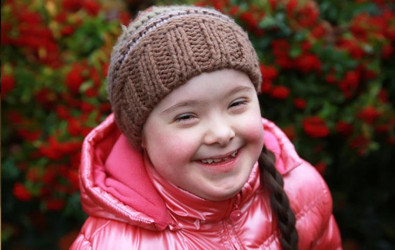 Girl smiling at camera outside.