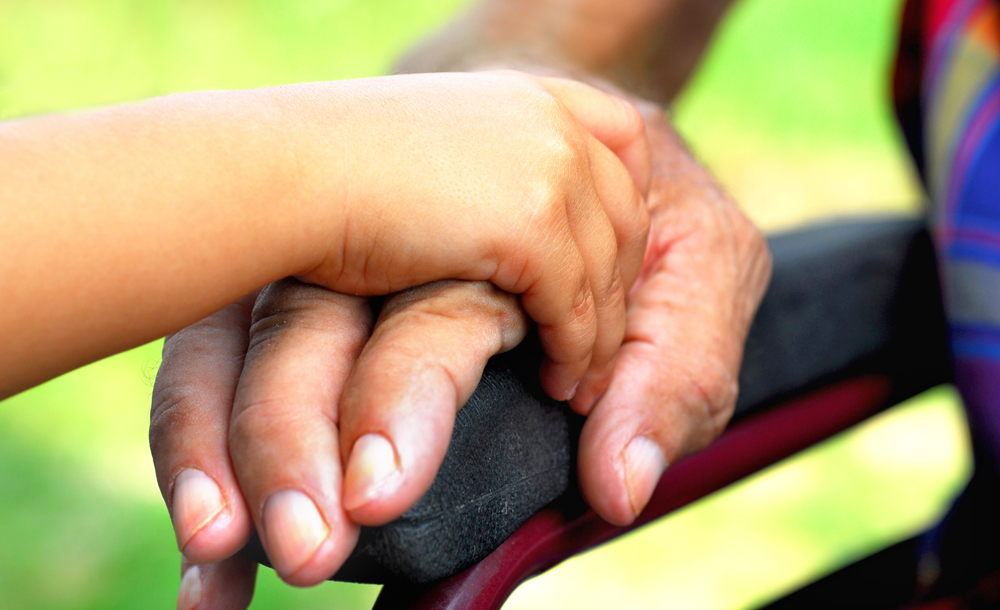 Close up of child's hand holding hand of elderly person in wheelchair.