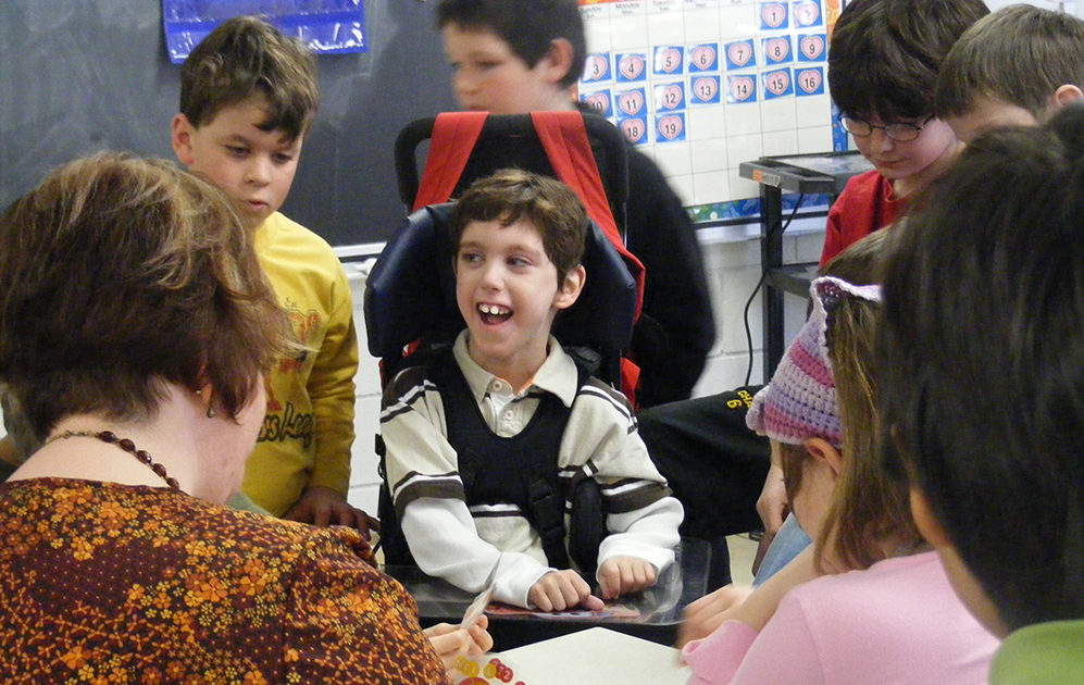 Young student in wheelchair included in classroom.