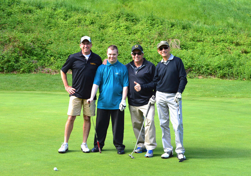 Four men, including one with Down syndrome, playing golf together.